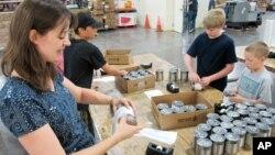Una maestra y sus alumnos ponen etiquetas a latas de comida para ser distribuidas entre familias de bajos ingresos en Nuevo México.