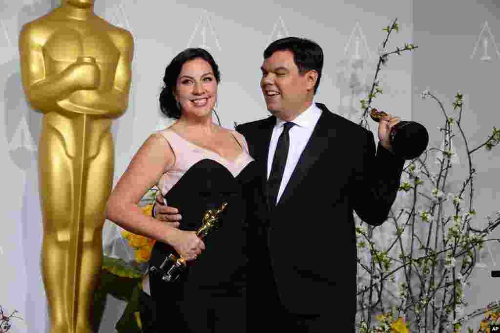"Kristen Anderson-Lopez, left, and Robert Lopez pose in the press room with their awards for best original song in a feature film for ""Let It Go"" from ""Frozen"" during the Oscars."