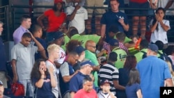 Fans look on as emergency medical personnel work on a fan who fell from an upper deck at Turner Field during a baseball game between New York Yankees and Atlanta Braves, Aug. 29, 2015, in Atlanta.