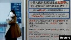 日本東京羽田機場一名戴著口罩的女子走過武漢肺炎的防疫廣告牌。(2020年1月20日)