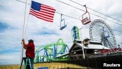Seorang pekerja mengibarkan bendera AS di pantai Seaside Heights setelah pantai-pantai di New Jersey dibuka kembali menjelang peringatan Hari Pahlawan atau Memorial Day di tengah pandemi virus corona, Seaside Heights, New Jersey, 23 Mei 2020. (Foto: Reuters)