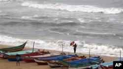 Seorang warga India berusaha memegang kuat payungnya saat angin kencang bertiup di kawasan pelabuhan Chennai, India selatan menjelang datangnya badai Nilam (30/10).