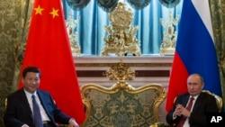 President w'igihugu c'Uburusiya, Vladimir Putin, mu buryo, ari kumwe na president w'igihugu c'Ubushinois, Xi Jinping, ku musi wa gatanu, itriki 22 z'ukwezi kwa gatatu, mu mwaka 2013