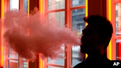 FILE - In this Feb. 20, 2014 file photo, a customer exhales vapor from an e-cigarette at a store in New York.