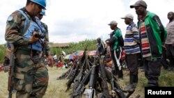 ARCHIVES - Des ex-combattants de groupes armés et milices déposent leurs armes aux pieds de casques bleus de la Mission des Nations unies en RDC, le 30 mai 2014.