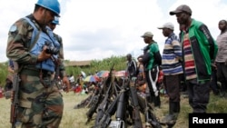 Des casques bleus ont récupéré quelques armes sur des comabattants Forces démocratiques pour la libération du Rwanda (FDLR) après leur reddition en Kateku, une petite ville dans la région orientale de la République démocratique du Congo (RDC), 30 mai 2014. United Nations peace keepers record details of weapons recovered from the Democratic Forces for the Liberation of Rwanda (FDLR) militants after their surrender in Kateku, a small town in eastern region of the Democratic Republic of Congo (DRC), May 30, 20