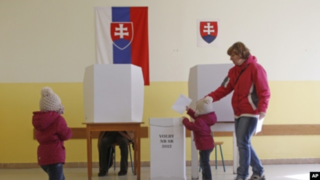 A child puts a vote in a ballot box during a general election in Bratislava, Slovakia, Saturday, March 10, 2012.