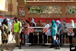 FILE - Egyptians wait to cast their votes outside a polling station during the Egyptian parliamentary election in Alexandria, Egypt, Oct. 18, 2015.