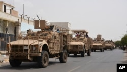 FILE - Yemeni pro-goverment forces fighting Houthi rebels are seen riding military vehicles on a street in the port city of Aden, Yemen, July 14, 2015.