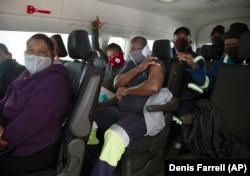 Orang-orang duduk di dalam kendaraan minibus sebelum divaksinasi, di Masjid Houghton, yang digunakan sebagai pusat vaksinasi COVID-19 drive-thru di Johannesburg Rabu, 28 Juli 2021. (Foto: AP/Denis Farrell)