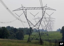 FILE - Electric lines extend over the hills of Owen County, near Owenton, Kentucky, July 22, 2011.