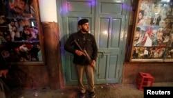 一名警察2月2日在巴基斯坦白沙瓦影院 外看守爆炸現場。