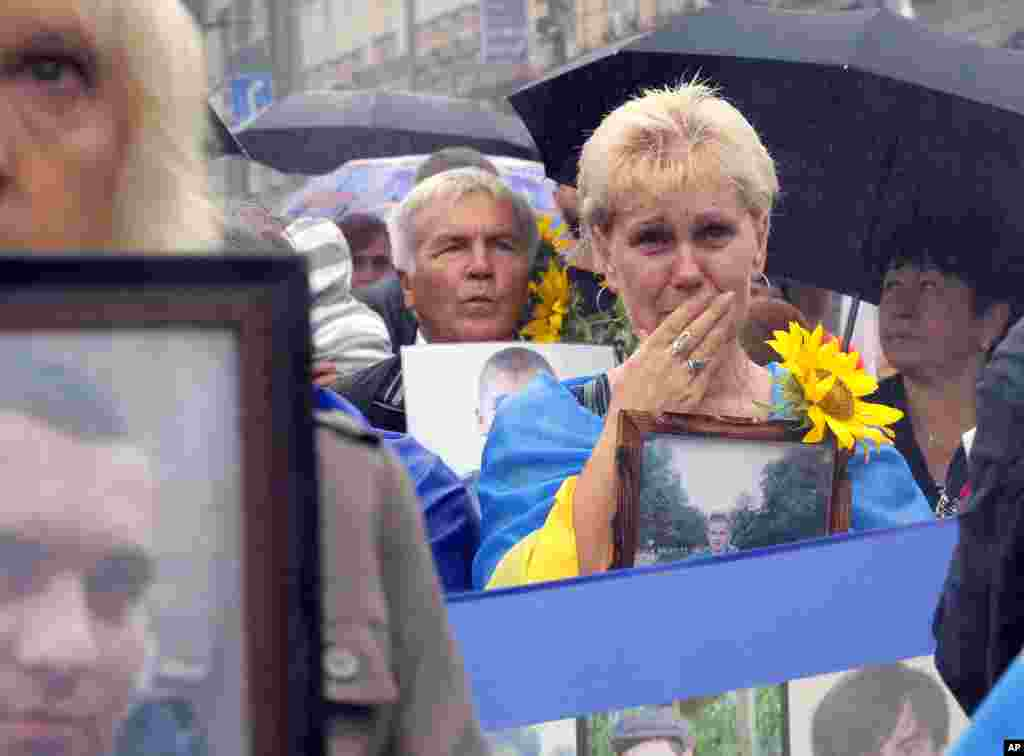 People hold photos of their relatives, who were killed in the conflict with pro-Russian separatists in the country's east, as they attend a rally for Independence Day in the Ukrainian capital Kyiv.
