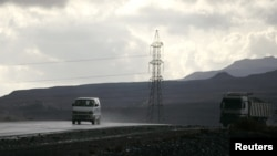 Vehicles drive past a high-voltage power line tower on a highway south of the Yemeni capital Sana'a February 26, 2010.