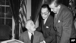 1941年10月10日,中国驻美大使胡适博士(中)向美国总统罗斯福(左)解说含有中国一万师生签名的书册