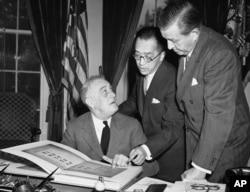 1941年10月10日,中國駐美大使胡適博士(中)向美國總統羅斯福(左)解說含有中 國一萬師生簽名的書冊 (資料圖片)