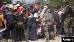 Polisi Makedonia berusaha mengatur para migran di stasiun kereta Gevgelija, Makedonia, Senin (7/9).
