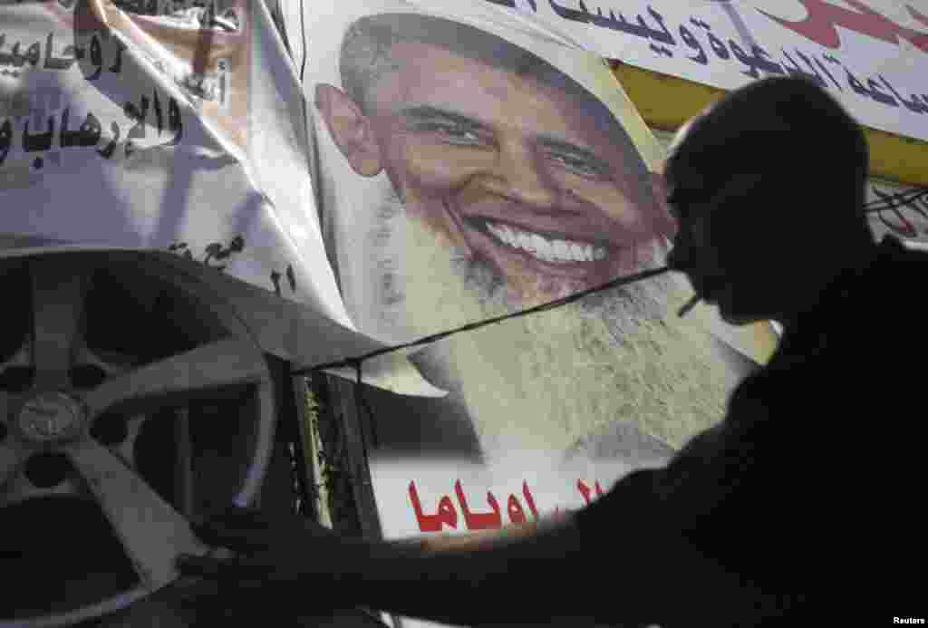 Salah Abdel Moneim, an anti-Morsi supporter of Egypt's army, works at his shop with a poster depicting U.S. president Barack Obama with a beard, Cairo August 7, 2013.