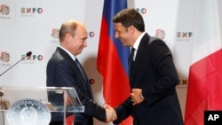 Italian Premier Matteo Renzi, right, shakes hands with Russian President Vladimir Putin at the end of a press conference at the 2015 Expo, in Rho, near Milan, June 10, 2015.