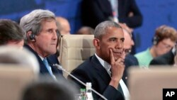 President Barack Obama waits next to State Secretary John Kerry for the start of the first working session of the North Atlantic Council at the NATO summit in Warsaw, Poland, Friday, July 8, 2016.