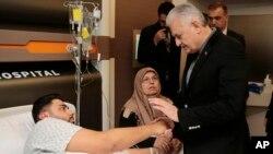 El primer ministro de Turquía, Binali Yildirim, habla con un hombre hospitalizado en Estambul, herido durante el ataque a una discoteca.