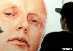 FILE - A man looks at a portrait of ex-spy Andrei Litvinenko by Russian artists Dmitry Vrubel and Viktoria Timofeyeva in the Marat Guelman gallery in Moscow.