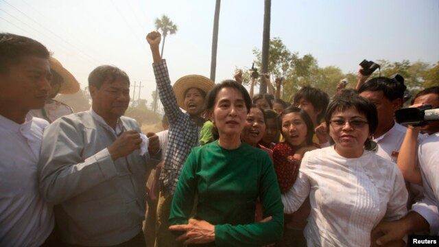 Burma pro-democracy Leader Aung San Suu Kyi poses for a photo as villagers protest against an investigation commission's report on a copper mine project in Sarlingyi township, March 14, 2013.