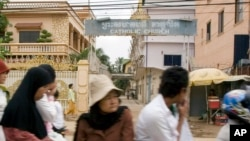Cambodians and Muslims ride on a motor-cart past a catholic church in Phnom Penh, Cambodia, Tuesday, July 17, 2007.