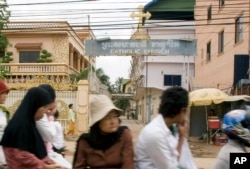 FILE - Cambodians and Muslims ride on a motor-cart past a catholic church in Phnom Penh, Cambodia, Tuesday, July 17, 2007.