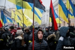 FILE - People attend a rally calling for Ukrainian lawmakers to recognize Russia as an aggressor state and support other anti-Russian legislative changes, near the Parliament building in Kyiv, Ukraine, Jan. 16, 2018.
