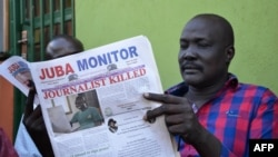 FILE - A man reads a copy of the Juba Monitor, with a heading referring to the killing of South Sudanese journalist Peter Moi of The New Nation newspaper, on August 21, 2015, in Juba.