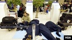 Para penumpang pesawat menunggu jadwal penerbangan mereka di terminal Charles-de-Gaulle Roissy, Paris, 24 Desember 2010.