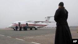 Un sacerdote ortodoxo observa un avión que lleva cadáveres de las víctimas de la caida del avión de Metrojet en Egipto.