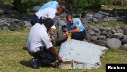 French gendarmes and police inspect a large piece of plane debris that was found on the beach in Saint-Andre, on Reunion Island in the Indian Ocean, July 29, 2015.