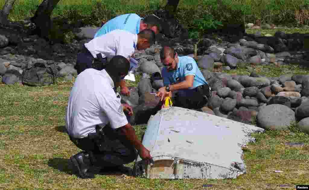 Des gendarmes et policiers français inspectent un morceau d'avion trouvé sur la plage de Saint-André, sur l'île de la Réunion, 29 juillet 2015.