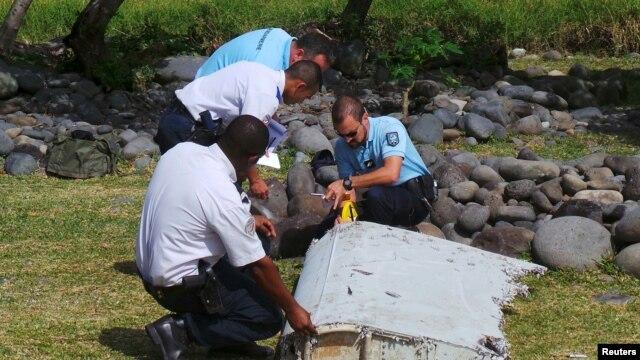 Gendarmes franceses examinan una pieza de los restos de un avión en la playa Saint-Andre, en la isla francesa La Reunión.