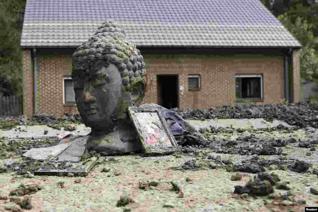 A statue of Buddha and storm debris are covered with mud outside a flooded house after heavy rains hit the town of Ittre, Belgium.