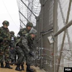 Jenderal Hwang Eui-don (kanan), Kepala Staf Gabungan Angkatan Bersenjata Korea Selatan, mengecek pagar di Zona Demilitarisasi antara kedua Korea selagi berpatroli bersama pasukan angkatan daratnya di Paju, Korea Selatan.