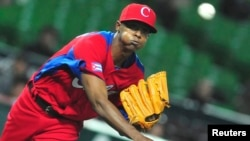 FILE - Cuba's Raciel Iglesias pitches a ball during the last preparation game for the World Baseball Classic (WBC) in Fukuoka, Japan, March 1, 2013. Iglesias failed to show up for training this week and was widely believed to have left the island.