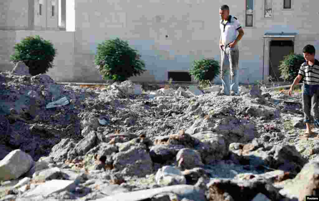Residents inspect the damage after what was said to be an air raid by Syrian government forces near Azaz, September 3, 2012.