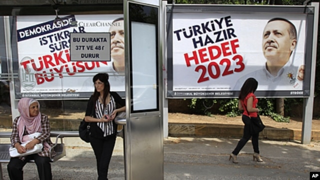 Commuters wait at a bus stop as posters of Turkish Prime Minister Recep Tayyip Erdogan are sen in the background in Istanbul, Turkey, June 10, 2011