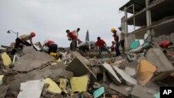 Para petugas penyelamat dan relawan mencari korban di antara reruntuhan bangunan di Pedernales, Ekuador, Minggu (17/4).