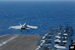 "FILE - In this May 3, 2019, photo released by the U.S. Navy, an F/A-18E Super Hornet launches from the flight deck of the aircraft carrier USS Abraham Lincoln. The U.S. sent the Lincoln and other military resources to the Middle East following ""clear indications"" that Iran and its proxy forces were preparing to possibly attack U.S. forces in the region, a defense official said on May 5, 2019."