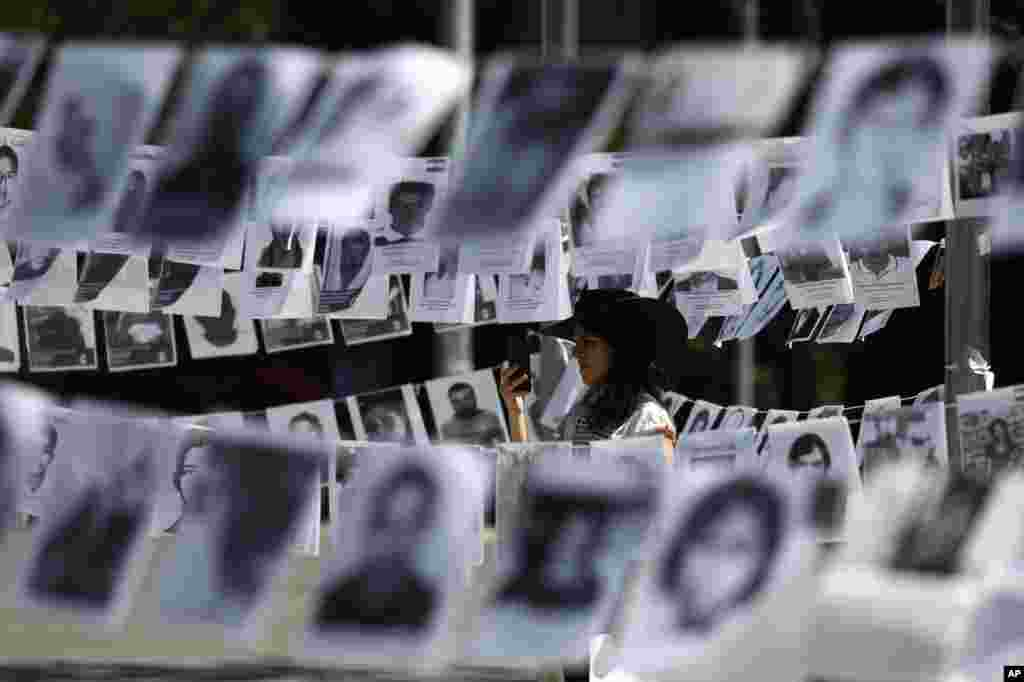 Framed by images of people who have been disappeared, a woman takes photos during a Mother's Day march in Mexico City, Mexico.
