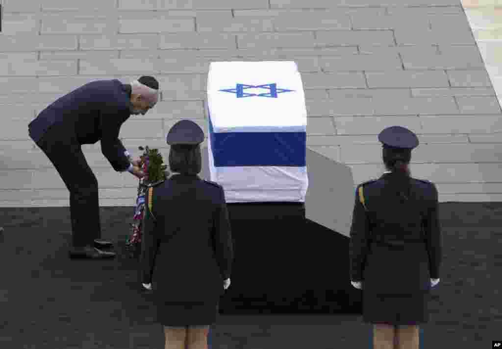 Presiden Israel Shimon Peres menaruh karangan bunga di atas peti jenazah mantan perdana menteri Israel Ariel Sharon di Plaza Knesset, Yerusalem, Minggu (12/1). Sharon, tokoh kontroversial yang dipuja sekaligus dibenci karena eksploitasi peperangan dan ambisinya untuk membentuk kembali Timur Tengah, meninggal dunia Sabtu, delapan tahun setelah terkena stroke yang membuatnya koma. Ia berusia 85 tahun. (AP/Oded Balilty)