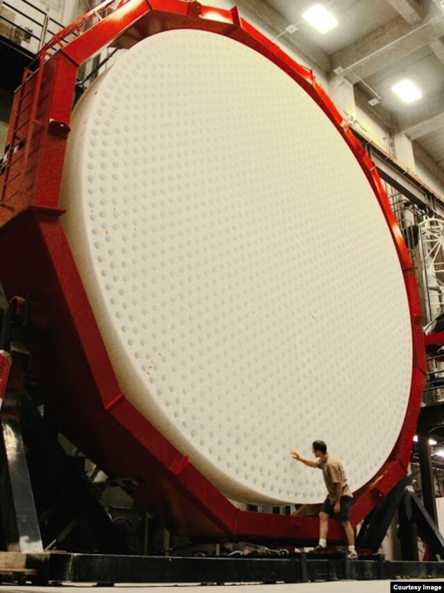 An observer with the Giant Magellan Telescope's third primary mirror. (Ray Bertram/University of Arizona)