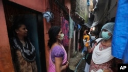 Técnicos de saúde medem a febre a residentes de Dharavi, um dos maiores bairros de lata da Ásia. Mumbai, Índia, 4 setembro, 2020