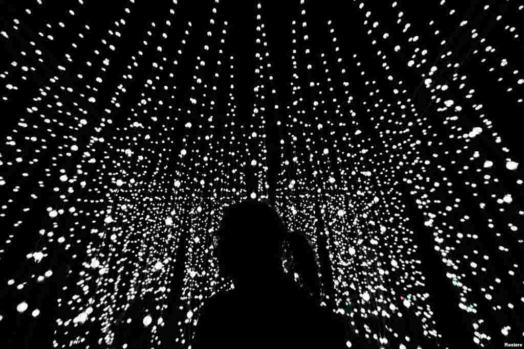A woman stands in front of an installation during a light festival in Prague, Czech Republic.