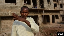 Prince Bala outside the half-finished construction where the IDPs are lodging. (VOA / K. Hoije)