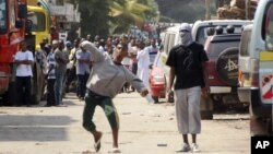 Muslim youth throw stones at riot police outside Masjid Musa Mosque in Mombasa, Kenya, Aug. 28, 2012.